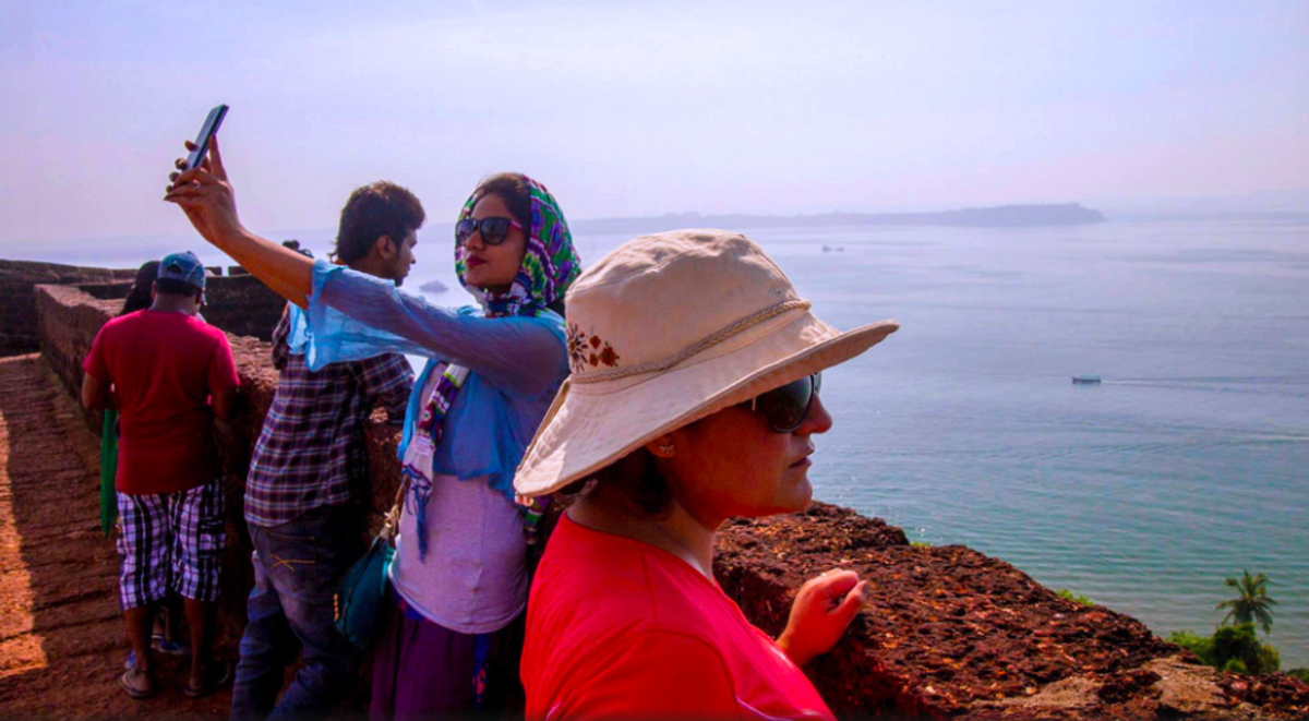 Tourists posing for selifes overlooking the Arabian Sea at Reis Magos Fort in the former Portuguese colony Goa, India.